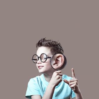 Chłopiec w niebieskiej koszulce i okularach przyłożył do ucha lupę w kolorze beżowym