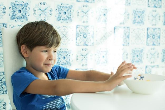 Chłopiec w niebieskiej koszulce je śniadanie z płatkami owsianymi i mlekiem na białym talerzu, miejsce na tekst, słaby apetyt, dziecko nie je