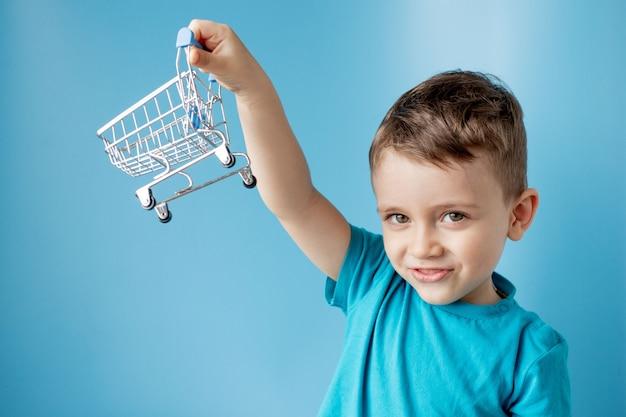 Chłopiec w niebieskiej koszulce trzyma wózek do kupowania towarów, produktów na niebiesko