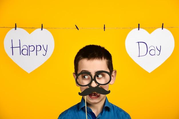 Chłopiec w niebieskiej koszuli na żółtym tle z sercem i napisem świąteczny dzień jest krzywy i ubiera okulary i wąsy