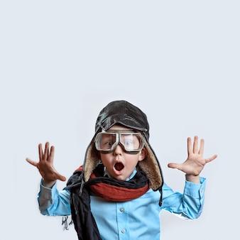 Chłopiec w niebieskiej koszuli, okularach pilota, kapeluszu i szaliku podniósł ręce
