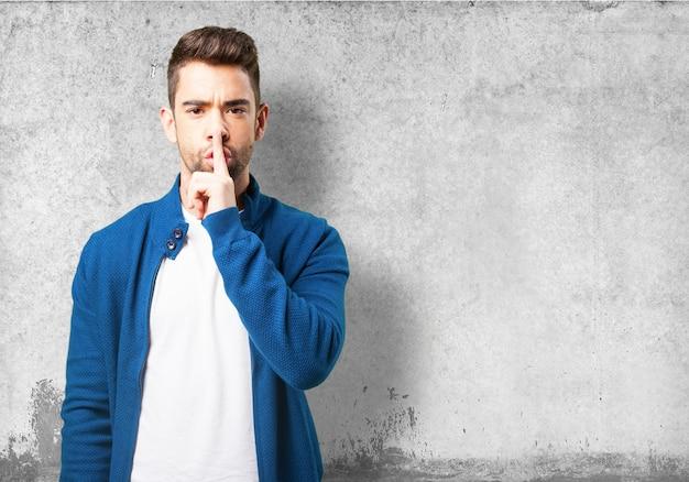 Chłopiec w niebieskiej kurtce z prośbą o ciszę