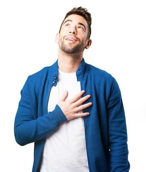 Chłopiec w niebieskiej kurtce z ręką w jego sercu