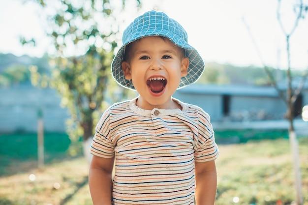 Chłopiec w niebieskim kapeluszu śmieje się z kamery
