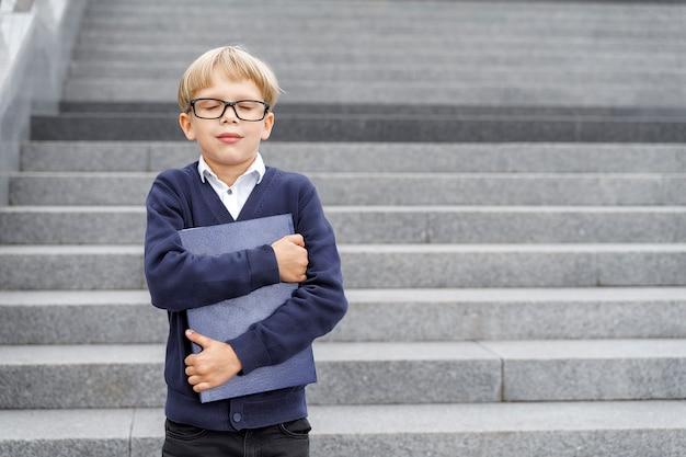 Chłopiec w niebieskim mundurze i okularach stoi na schodach z niebieskim notesem