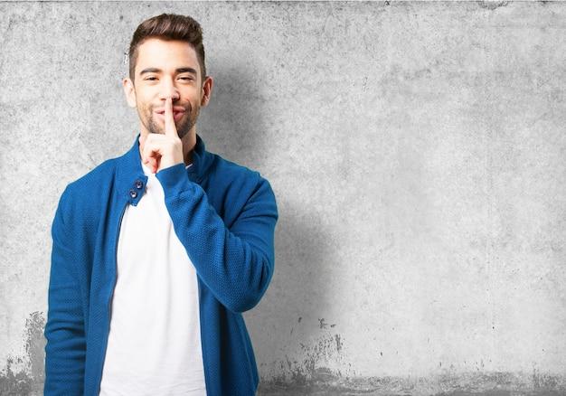 Chłopiec w niebieskim płaszczu, uśmiechając się i prosząc o ciszę