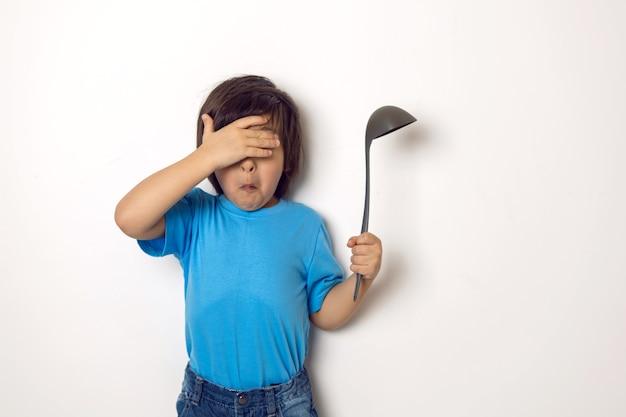 Chłopiec w niebieskim t-shircie zakrył oczy ręką stoi z chochlą na białej ścianie
