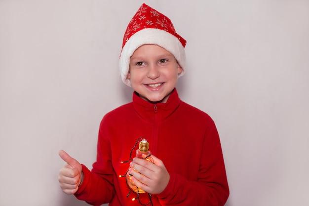 Chłopiec w noworocznym kapeluszu z magiczną lampką