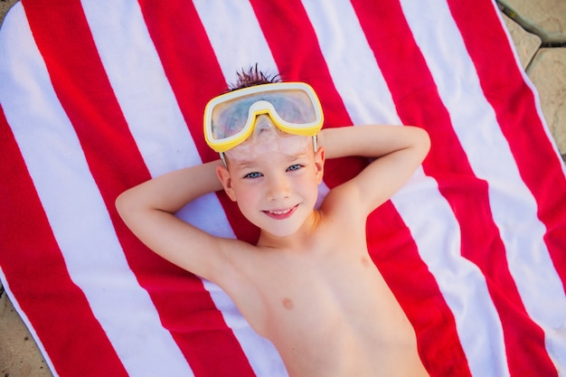 Chłopiec w nurkowych gogle kłama na czerwonym i białym ręcznik plażowy i ono uśmiecha się