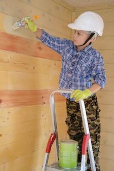 Chłopiec w ochronnej farbie maluje ścianę drewnianego domu stojącego na drabinie. malowanie drewnianego domu od wewnątrz olejem do drewna