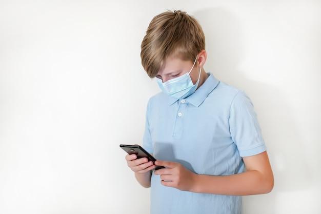 Chłopiec w ochronnej masce na twarz gra na smartfonie w grze online. uczeń ogląda pracę domową na telefonie podczas kwarantanny koronawirusa