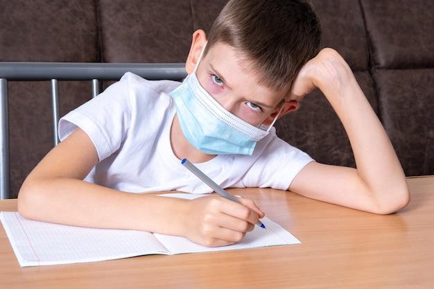 Chłopiec w ochronnej masce na twarzy patrzy na ciebie z niezadowoleniem, dziecko nie chce uczyć się online w domu. koncepcja edukacji online, kształcenie na odległość