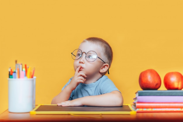 Chłopiec w okrągłych okularach w koszuli i siedzi przy biurku i myślenia