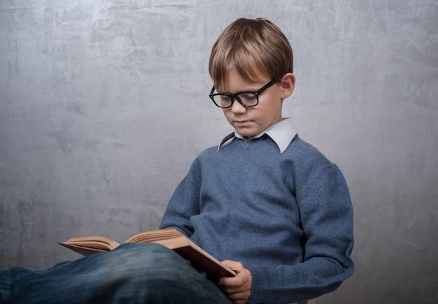 Chłopiec w okularach, czytając książkę, siedząc na krześle w pokoju