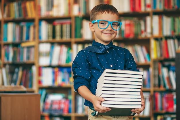 Chłopiec w okularach i stos książek