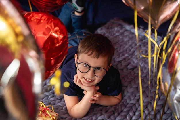 Chłopiec w okularach marzy, leżąc na łóżku