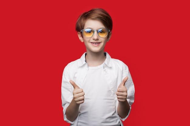 Chłopiec w okularach pokazuje podobny znak