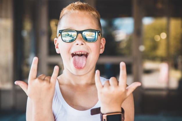 Chłopiec w okularach przeciwsłonecznych wystawia język.