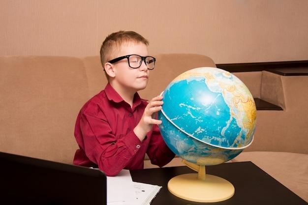 Chłopiec w okularach siedzi przy czarnym stole
