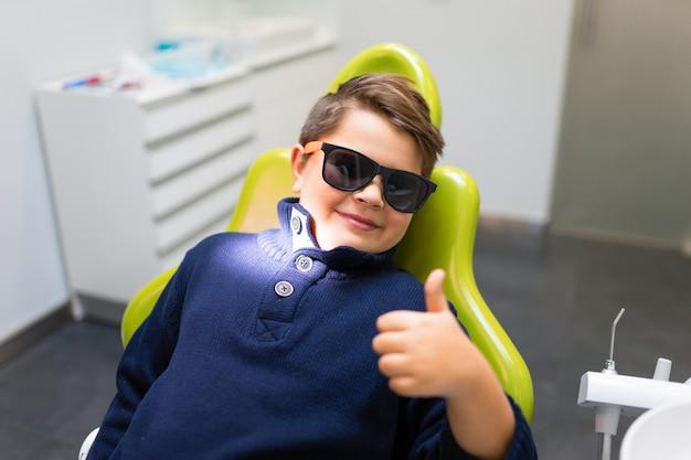 Chłopiec w okularach siedzi w fotelu dentystycznym i pokazuje kciuk do góry