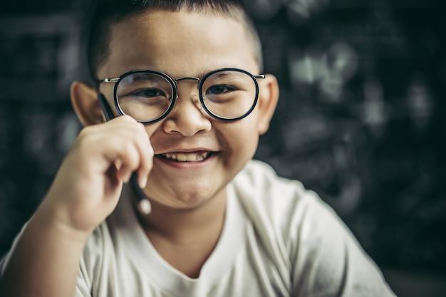 Chłopiec w okularach siedzi w klasie, studiując