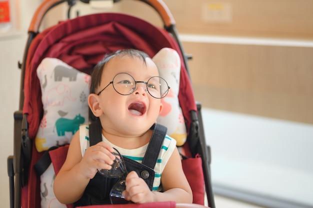 Chłopiec w okularach siedzi w nowoczesnym wózku. podróżowanie z małymi dziećmi. transport dla rodziny z niemowlakiem.
