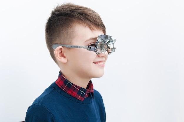 Chłopiec w okularach sprawdza wzrok u okulisty