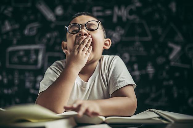 Chłopiec w okularach studiujący i senny.