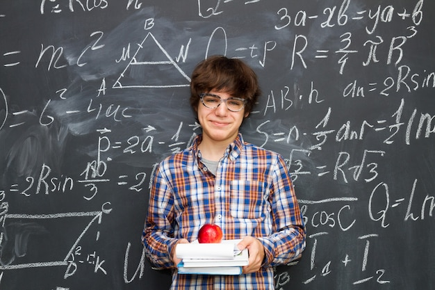 Chłopiec w okularach, trzymając książki z jabłkiem, tablica wypełniona formułami matematycznymi w tle