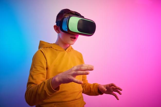 Chłopiec w okularach wirtualnej rzeczywistości na kolorowym tle. technologia przyszłości, koncepcja vr
