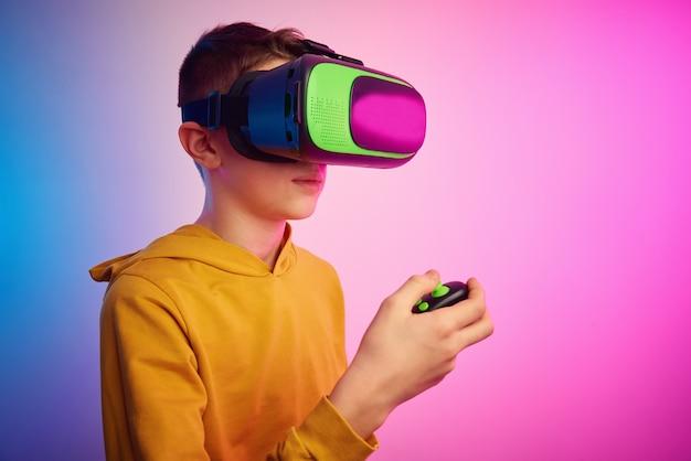 Chłopiec w okularach wirtualnej rzeczywistości na kolorowym tle