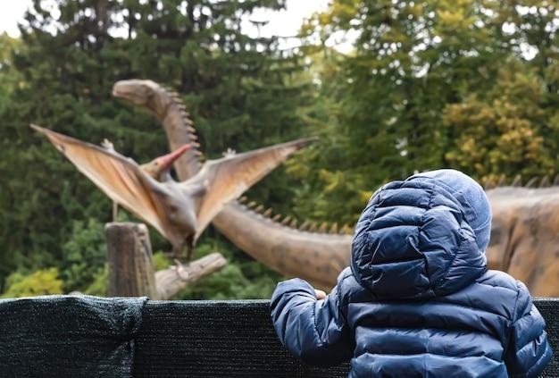 Chłopiec w parku dinozaurów