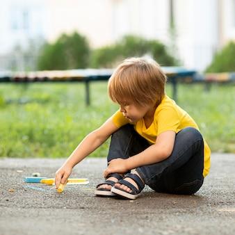 Chłopiec w parku, rysowanie kredą