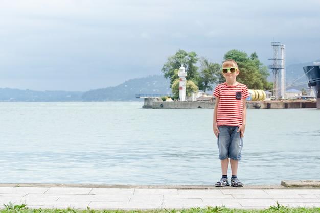 Chłopiec w pasiastej koszulce i okularach stoi na tle morza i małej latarni morskiej