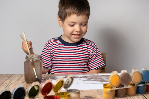 Chłopiec w pasiastym t-shircie rysuje farbami gwaszowymi