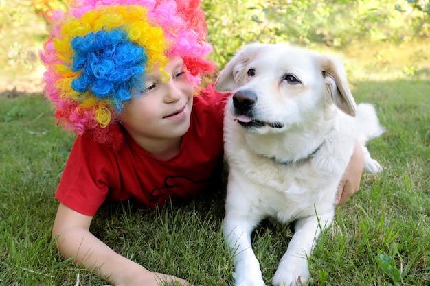 Chłopiec w peruce klauna przytula psa.