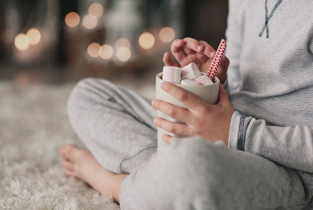 Chłopiec w piżamie pije gorącą czekoladę