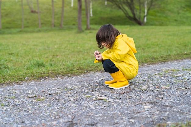 Chłopiec w płaszczu przeciwdeszczowym i żółtych kaloszach przykucnięty bawiąc się kamieniami na ziemi