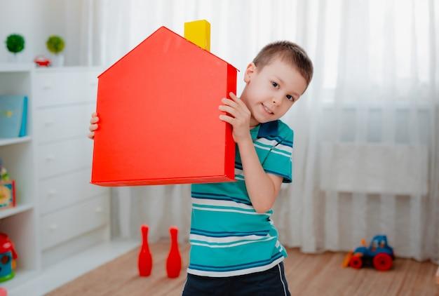 Chłopiec w przedszkolu z czerwonym domkiem z zabawkami
