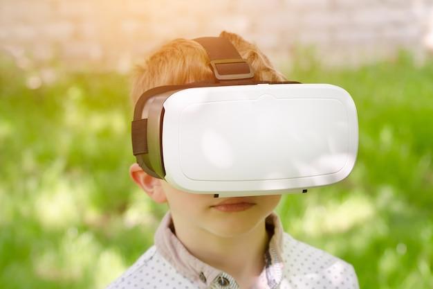 Chłopiec w rzeczywistość wirtualna hełmie na tle zielona trawa