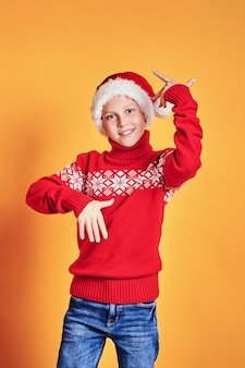 Chłopiec w santa kapeluszu pokazuje aprobaty na kolorze żółtym