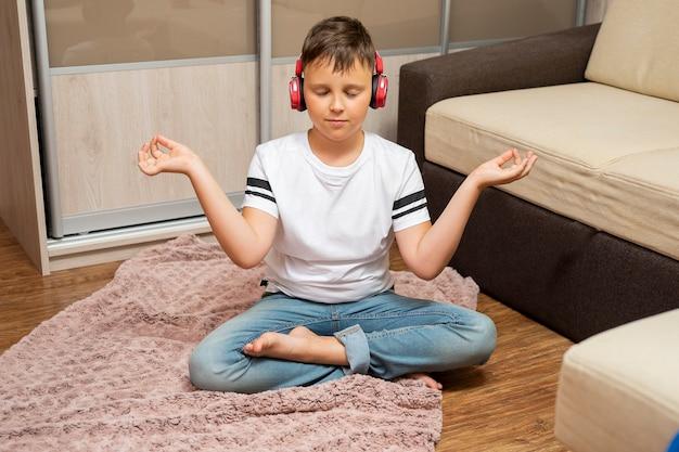 Chłopiec w słuchawkach, słuchanie muzyki. leży obok sofy. medytuje i cieszy się.