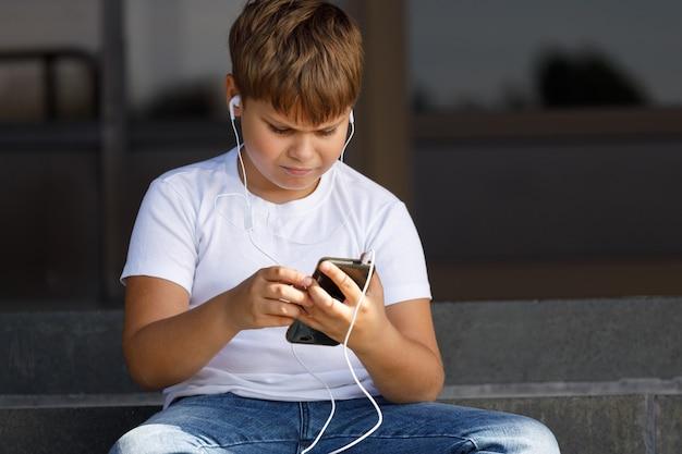 Chłopiec w słuchawkach ze smartfonem słucha muzyki w parku