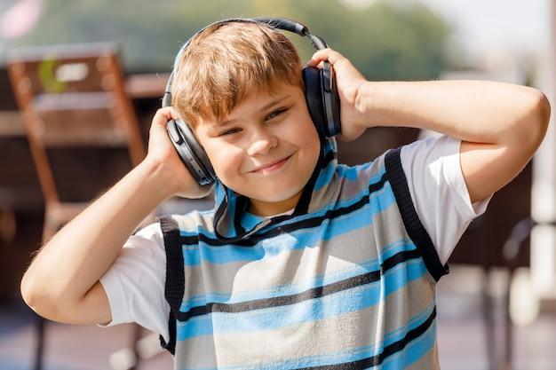 Chłopiec w słuchawkach ze smartfonem, słuchanie muzyki w parku