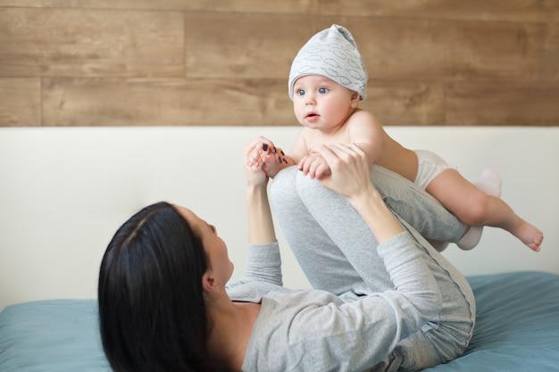 Chłopiec w śmiesznej nakrętce robi ćwiczeniom z jego matką
