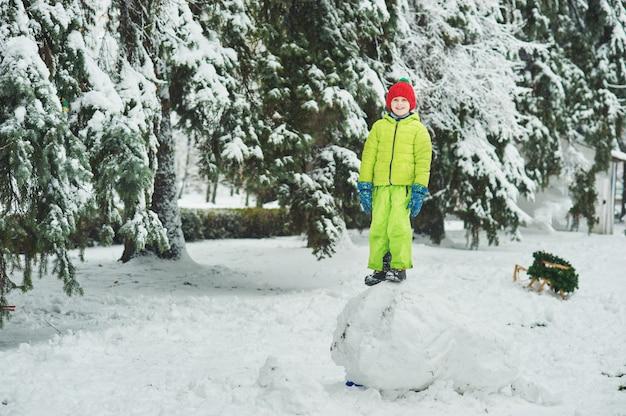 Chłopiec w śniegu w parku. chłopiec bawi się w winter park. uroczego dziecka odprowadzenie w śnieżnym zima lesie