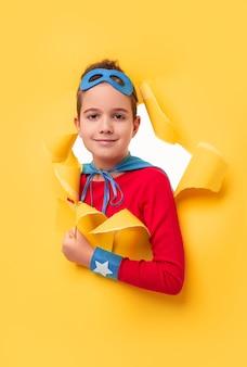 Chłopiec w stroju superbohatera, uśmiechając się i patrząc na kamery, wyglądając przez dziurę rozdartą w jasnożółtym papierze