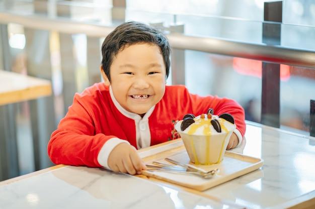 Chłopiec w stroju świętego mikołaja i jego lody oreo uśmiechnął się i był szczęśliwy.