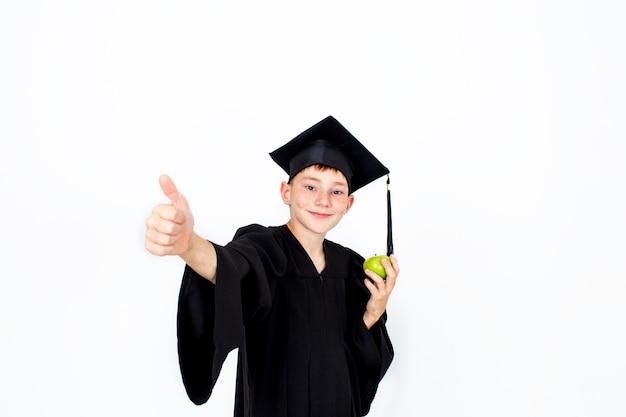 Chłopiec w studenckim kapeluszu z jabłkiem w dłoni
