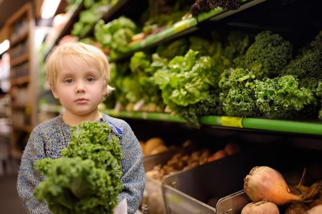 Chłopiec w supermarkecie wybiera świeżego organicznie kale